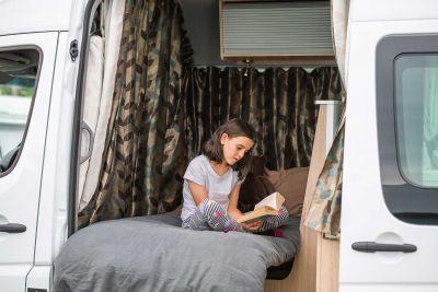 Schmökern im Bett des Campervans Venturer Plus von Britz Neuseeland