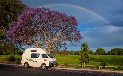 Camper Endeavour von Hippie Neuseeland unter Blüten und Regenbogen
